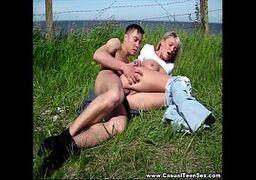 Mulher fazendo sexo na grama com o seu macho que lhe coloca de ladinho e então empurra a benga nela com força